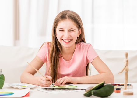 Girl smiles when drawing green avocado