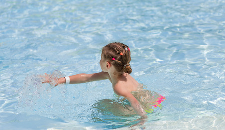 Little girl playing in transparent water Banque d'images