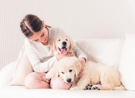 Smiling girl hugging puppies