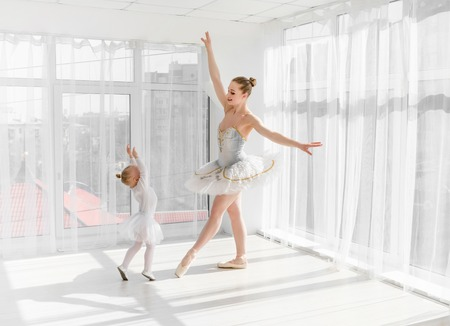 Young gorgeous ballerina with her little daughter dancing in studio Zdjęcie Seryjne