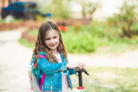 Little girl riding on scooter
