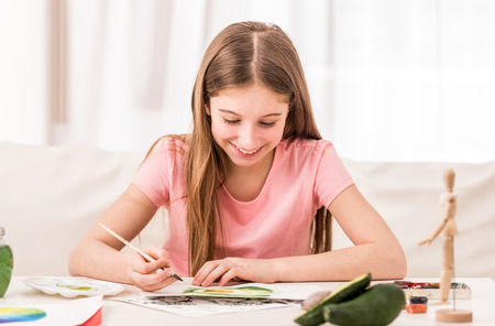 Girl smiles when drawing green avocado Stok Fotoğraf - 122288522