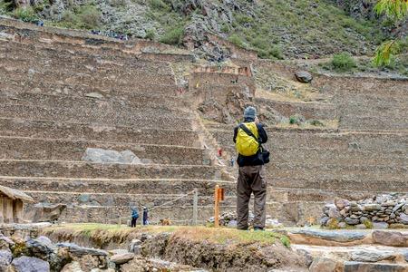 Tourist taking photo of Ollantaytambo terraces