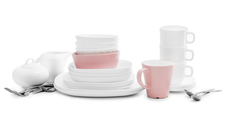 White and pink plates, sugar bowl and mugs on light background Фото со стока