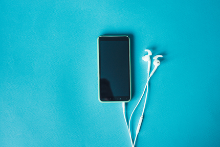 Modern smartphone with white earphone on blue textured background with copy space Фото со стока