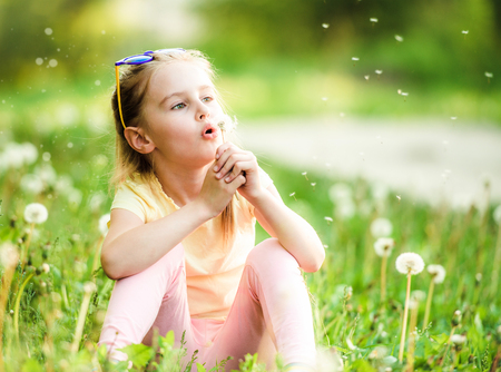 Cute girl playing with dandelions 스톡 콘텐츠 - 124175205