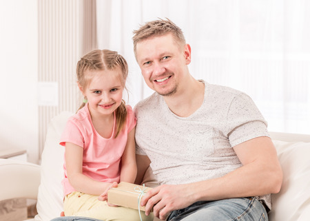 Dad with daughter opening Fathers day gift on sofa