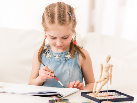 Little girl isdraws with watercolors