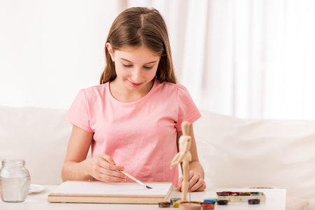 Girl drawing from figure with paint