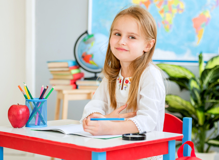 Little blond girl sit at the white desk and laughing in the school classroom 스톡 콘텐츠 - 124175143
