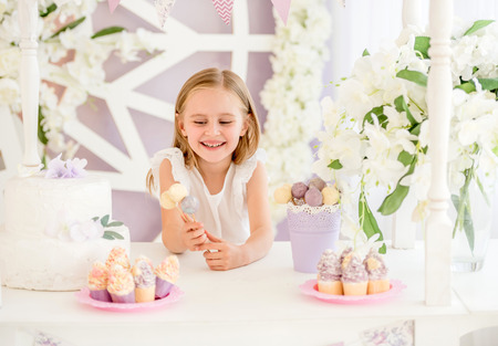 Little girl holding colorful sweet lollipops in the candy bar