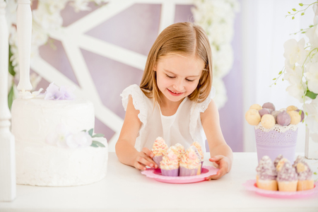 Little girl holding a pink plate with sweet cakes in the candy bar Фото со стока