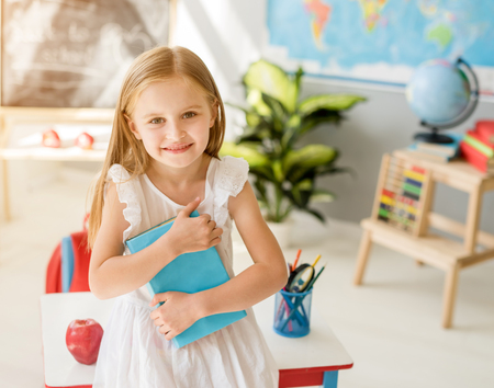 Little smiling blond girl standing in the school classroom 스톡 콘텐츠 - 124175146