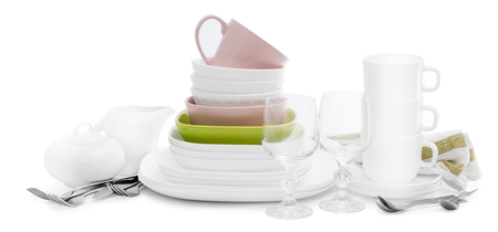 Stack of white ceramic kitchenware and cutlery, isolated on white