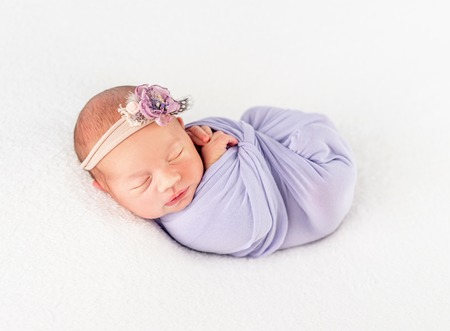 Infant newborn in flowery band and blanket, secured with a braid 스톡 콘텐츠 - 124175112