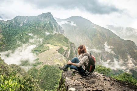 Girl-hiker looking on top of Huayna Picchu, looking on Machu Picchu 스톡 콘텐츠 - 124175079