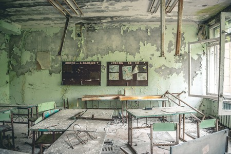 ruiniertes Klassenzimmer mit Schreibtischen und Tafeln in der Pripyat-Schule