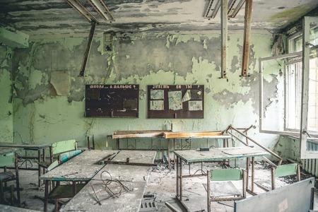 Salle de classe en ruine avec des bureaux et des tableaux noirs à l'école de Pripyat