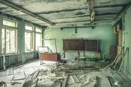ruined class room with desks and blackboards in Pripyat school