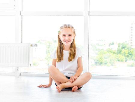 Bambina sorridente, seduta per terra