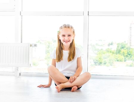 Female kid smiling, sitting on the floor Stockfoto