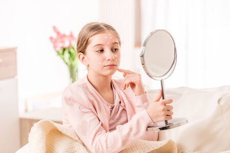 Girl with chickenpox looking at the mirror Stock Photo