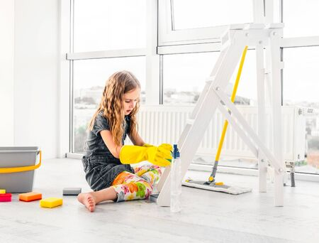 Little girl scrubbing the room in rubber gloves