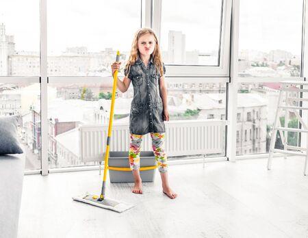 Little girl moping floor in the living room Standard-Bild