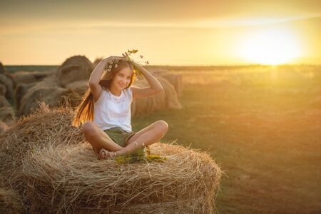 Lovely teen girl with floral bouquet, on haystack Stock fotó