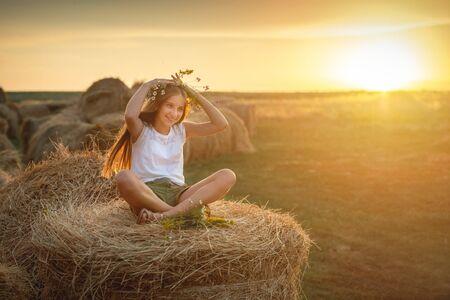 Lovely teen girl with floral bouquet, on haystack Reklamní fotografie