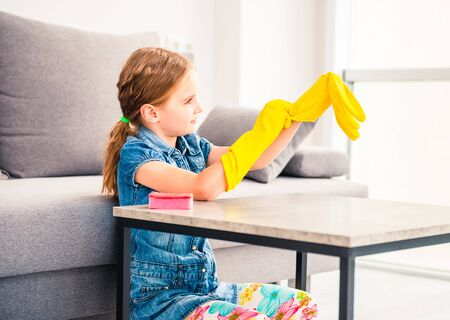 Little girl putting on rubber gloves for chores