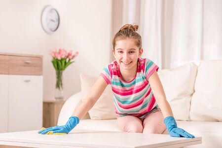 Girl scrubbing table clean