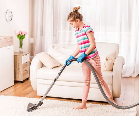 Girl is cleaning carpet Stock Photo