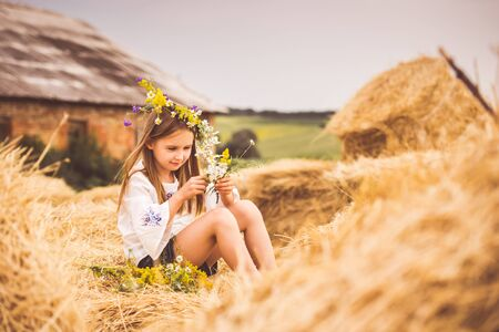 Little girl making floral band on haystack