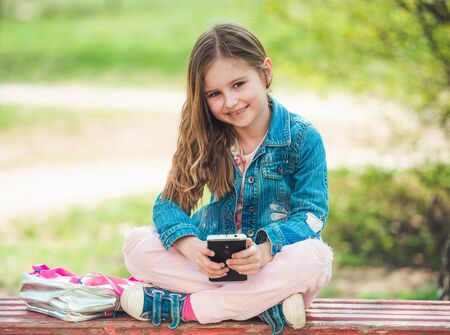 Little girl sits with her phone in park