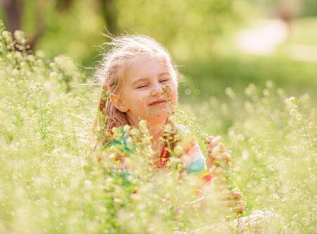 Child resting on green field 스톡 콘텐츠