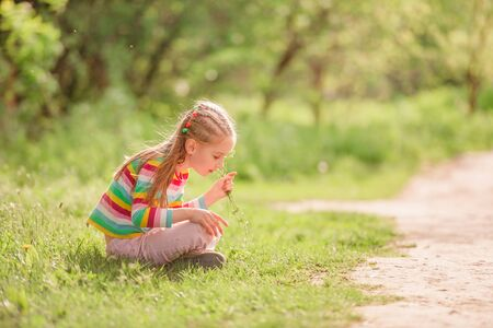 Child sitting near road with flower