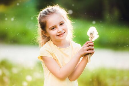 Cute little girl collecting flowers