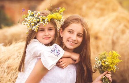 Two cute sisters with flowers