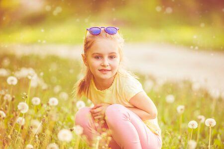 Pretty kid gorl sitting on green field 스톡 콘텐츠