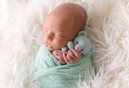 Newborn baby lying with knitted toy Archivio Fotografico - 127053307