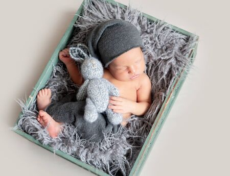 Newborn baby sleeping in crate with wool 스톡 콘텐츠