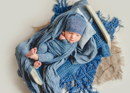 Sweet newborn lying on little kids bed 스톡 콘텐츠