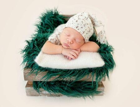 Dreamy newborn baby sleeping on bed