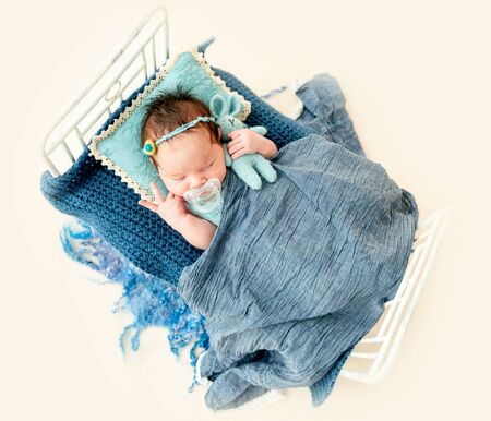 newborn baby girl sleeping in a little bed Reklamní fotografie