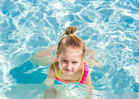 Smiling girl swim to the poolside