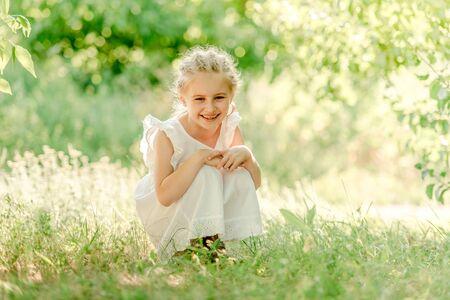 Fille d'âge préscolaire assise sur l'herbe Banque d'images