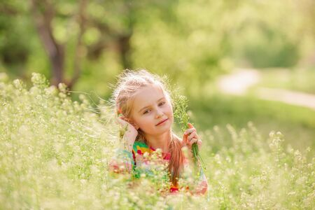 Child resting on green field 写真素材