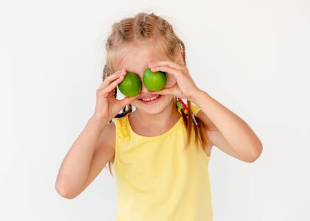 Little girl with fresh lime fruits
