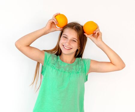 Little girl with fresh orange fruits